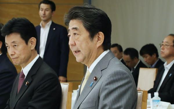 経済財政諮問会議に出席する安倍首相。左は西村経財相(9月30日、首相官邸)