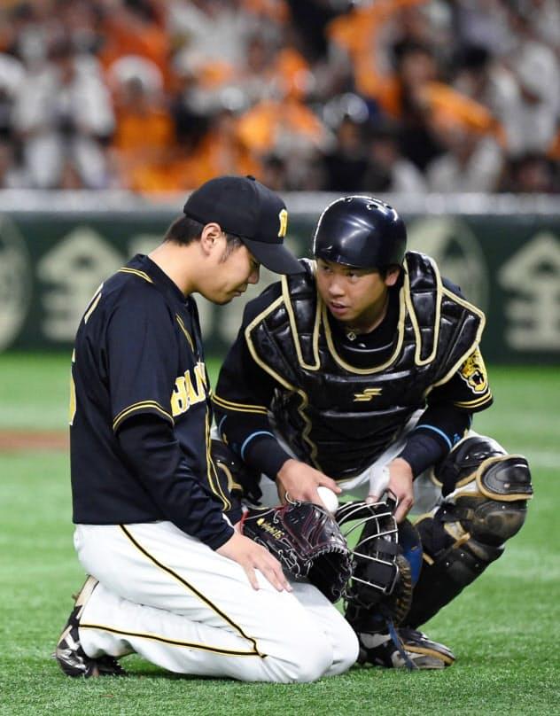六回、梅野(右)に声を掛けられる、勝ち越しを許した阪神・西