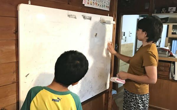 生駒さんは自宅の居間のホワイトボードを使って次男(左)に勉強を教える                                                   (川崎市)