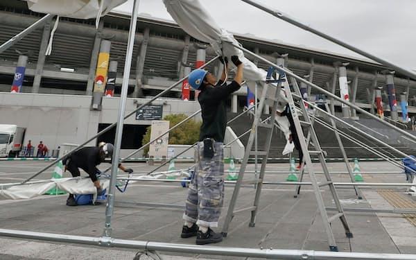 横浜国際総合競技場前のテントで台風対策する作業員(10日、横浜市)