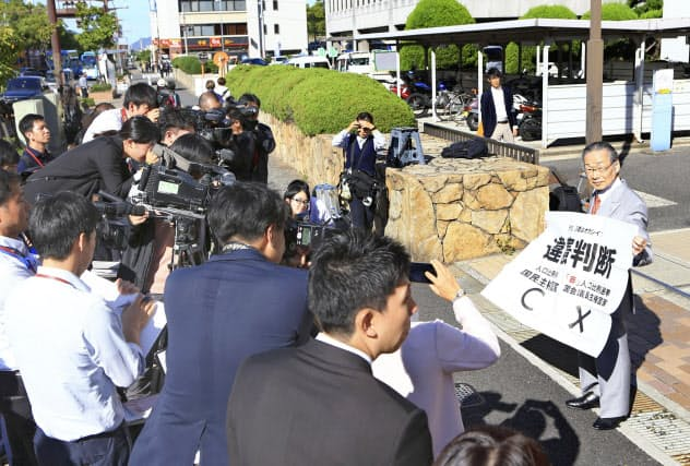 「違憲判断」と書かれた紙を掲げる原告側の升永弁護士(右)=16日、高松高裁