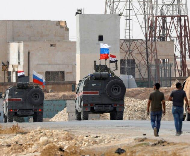 15日、シリア北部マンビジュ近郊ではロシアの国旗がはためいていた=ロイター