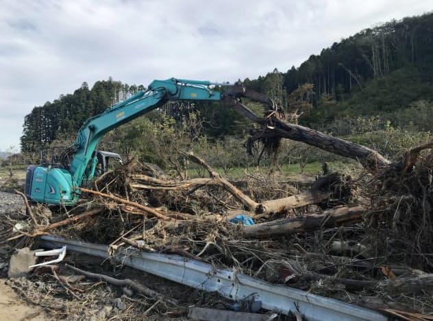 川に集積した流木を撤去する重機(17日、宮城県角田市)