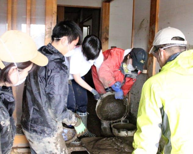 家屋にたまった泥を運び出すボランティアの人たち(19日、長野市)