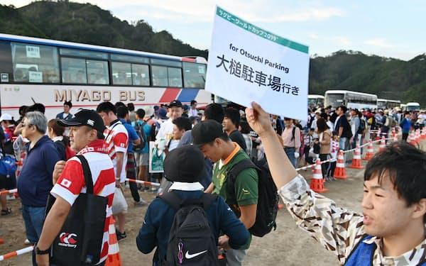 釜石鵜住居復興スタジアムから駐車場へ向かうシャトルバスを待つ人たち(9月25日、岩手県釜石市)