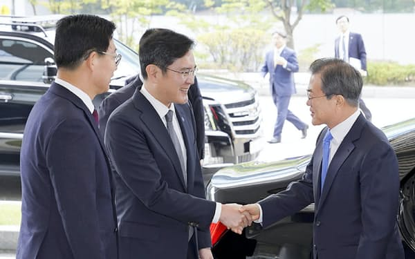 韓国政府は部品・素材国産化へ大手財閥を巻きこむ(サムスン電子の李在鎔副会長と握手する文在寅大統領(右))=大統領府提供