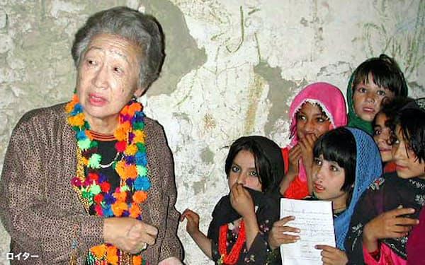 2000年9月、パキスタンのアフガニスタン難民キャンプで、子供たちから手作りのハンカチを受け取る緒方国連難民高等弁務官=ロイター共同