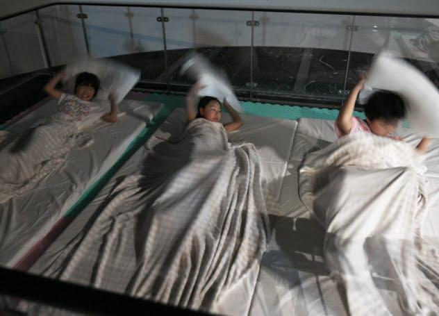 夜間の就寝時を想定した地震体験をする参加者(東京都豊島区の池袋防災館)