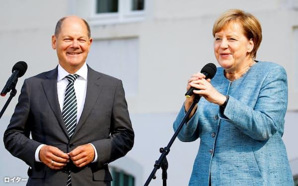 メルケル氏(右)の後継争いをにらむショルツ氏は「欧州共通の預金保険を創設すべきだ」と主張=ロイター