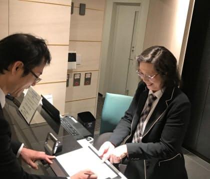 パソコン作業の傍ら、来訪者に手際良く応対する(東京都港区)