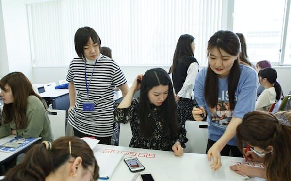 TAと議論し、課題の解決策などをまとめ、発表に備える学生ら(東京都世田谷区)=昭和女子大提供