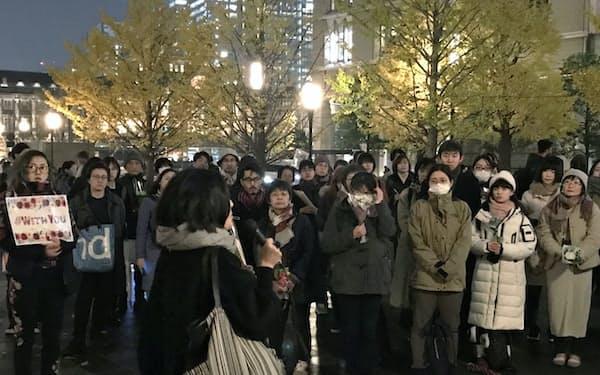 花を手にして、スピーチを聞く参加者ら(11日、東京駅前)