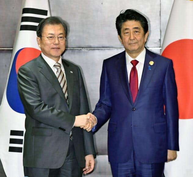 会談前に握手する文大統領(左)と安倍首相(24日、中国・成都)=共同