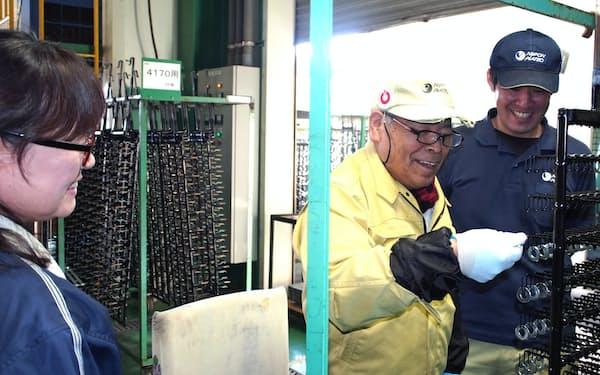 小林光江ジョブコーチ(左)の助言を受けながら職場に復帰した蓮実敬三さん。及川勝彦日本プレーテック取締役(右)が見守る(19年12月、栃木県那須塩原市)