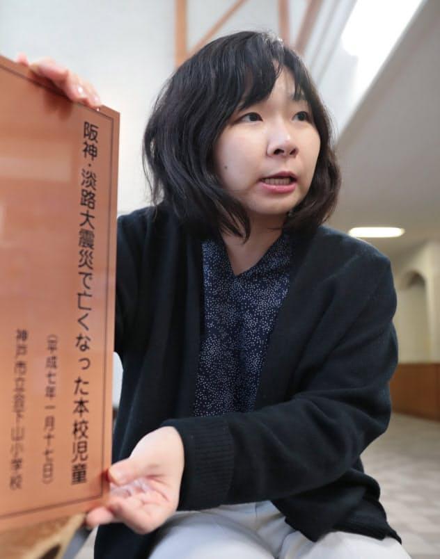 亡くなった同級生の名前が刻まれた銅板を手に語る山本さん(7日、神戸市の会下山小学校)