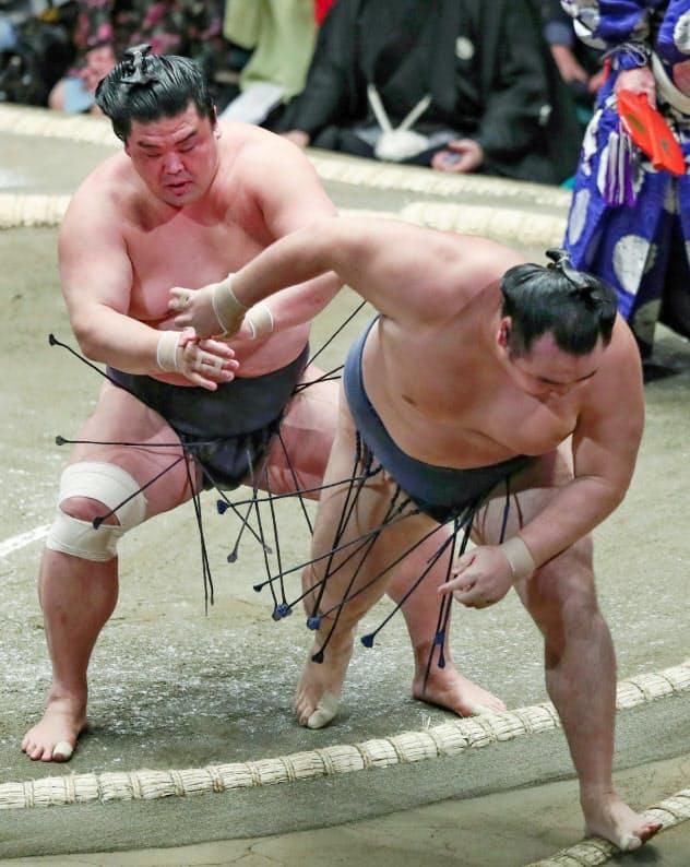 妙義龍(左)は鶴竜を破った 〔時事〕