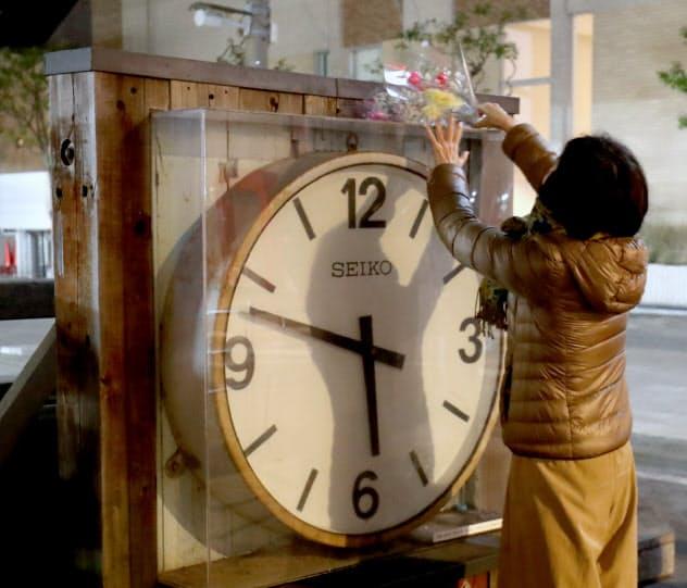 震災から25年、発生時刻を指して止まったままの時計に花を供える人(17日午前、兵庫県西宮市)