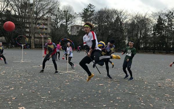 クィディッチはホウキに見立てた棒などにまたがって競う(東京都品川区、中央が原田さん)