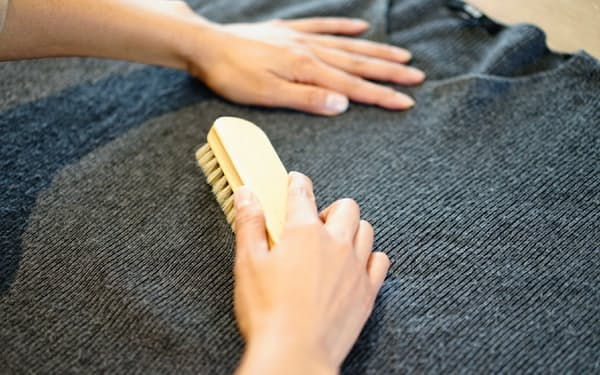 豚毛の洋服ブラシで繊維の絡まりをほぐす