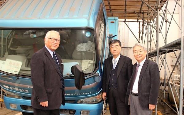 東京都市大が実験に使った水素ハイブリッドトラックとiLaboの創業メンバー(左から岩崎氏、山根氏、中山氏)