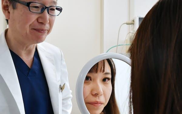 手術後、鏡で自分の目を見る女性会社員(東京都中央区)