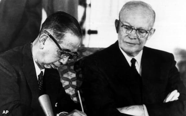 1960年、日米安保条約の改定で署名する岸信介首相と見守るアイゼンハワー大統領=AP