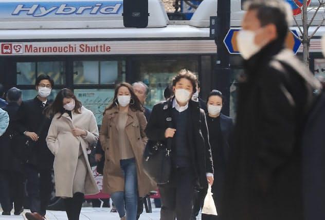 マスク姿でオフィス街を歩く人たち(26日午前、東京都千代田区)
