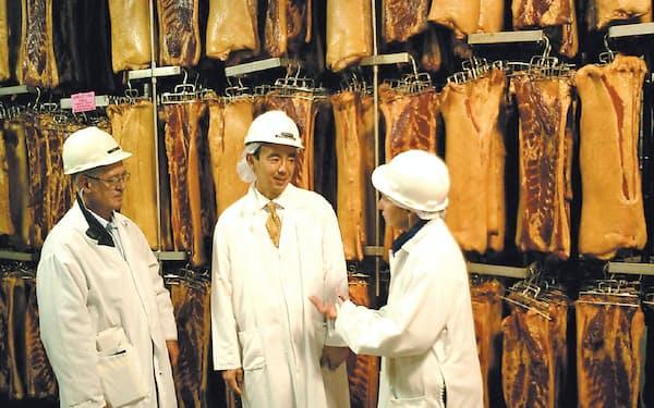 米国赴任時代、インディアナの精肉加工工場で(中央が竹増さん)