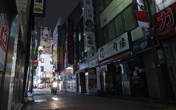 金曜の夜にもかかわらず明かりが消えた繁華街(17日、東京都新宿区の歌舞伎町)
