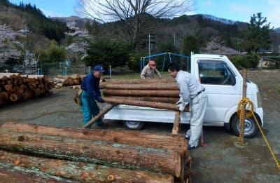町民から買い取った木材をトラックからおろす町職員ら(4月、群馬県中之条町)