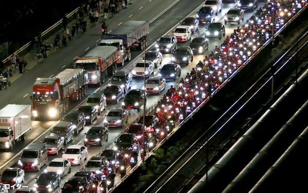 マレーシアが国境を封鎖する直前、シンガポールに殺到する車や人=ロイター