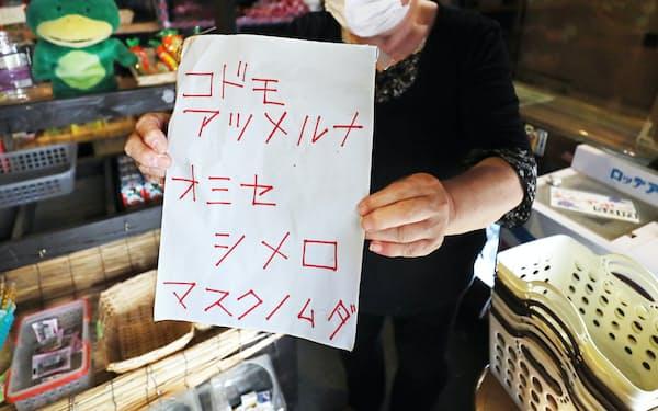 店の入り口に貼られていた紙を手にする店主の村山さん(千葉県八千代市)