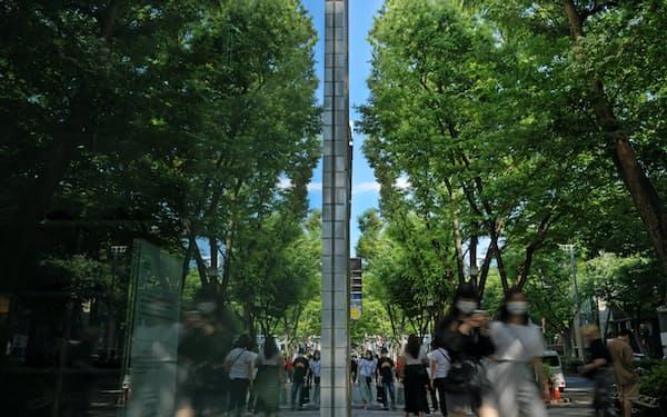 ケヤキ並木の緑に染まる表参道とマスク姿の人々が、店のショーウインドーに映る=浦田晃之介撮影