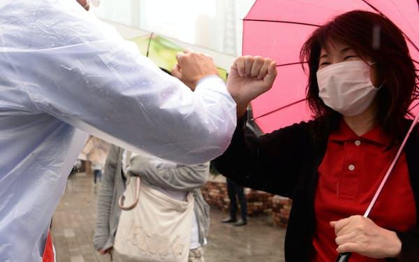 街頭で肘を合わせて支持を訴える都知事選立候補者(左)(19日、東京都港区)