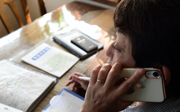 一人暮らしの高齢者に電話で近況を聞く藤原さん(東京都世田谷区)