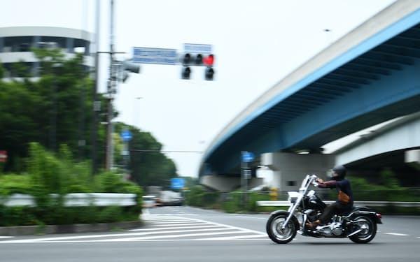 環七大井ふ頭の交差点。薄曇りの夏の空の下を、1台のオートバイが走り去る=中岡詩保子撮影