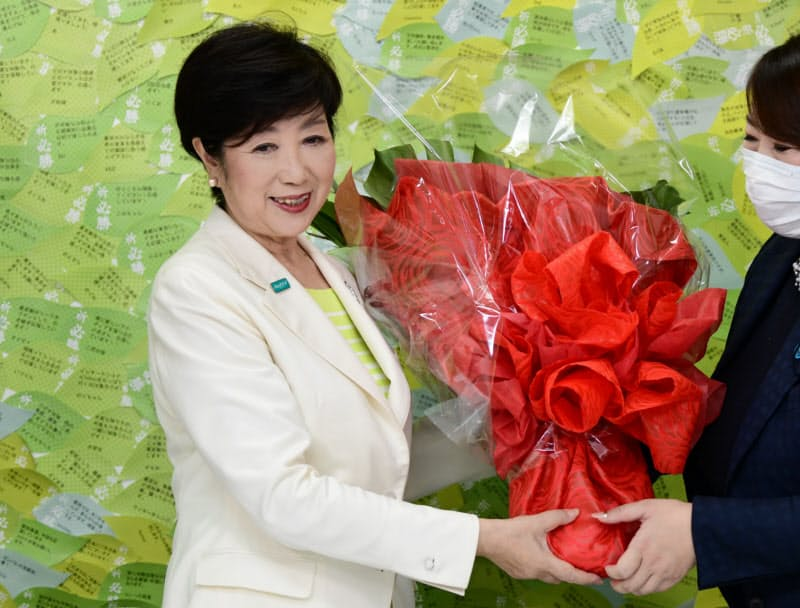 当選を決め、関係者から花束を受け取る小池氏(左)(5日、東京都新宿区)