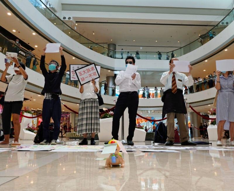 取り締まりを避けるため、白紙を掲げて抗議する人たち(6日、香港)=ロイター