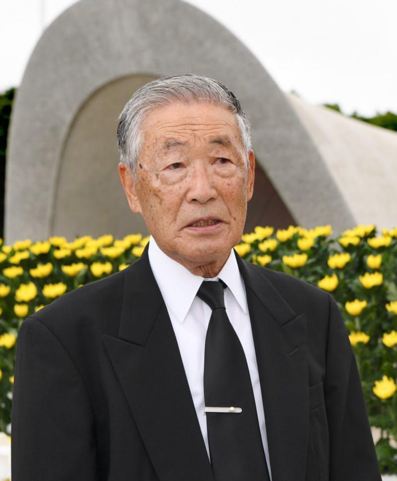 上平和記念式典に参列した被爆者代表の吉川さん 下原爆慰霊碑に向かい手を合わせる人たち (6日午前、広島市の平和記念公園)
