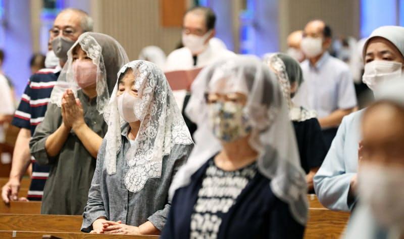 マスクを着用し、追悼ミサで祈りをささげる人たち(9日、長崎市の浦上天主堂)