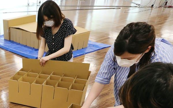 避難所で使う段ボールベッドを組み立てる学生(東京都世田谷区)