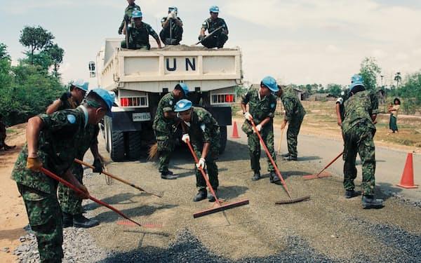 (写真は1992年9月、カンボジアPKOで作業する自衛隊=内閣府提供)