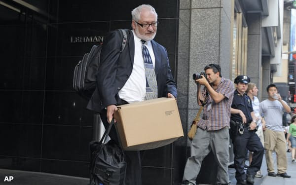 ニューヨークの本社ビルから荷物をまとめて出てくる男性=AP