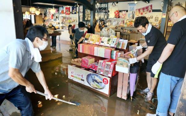 (台風18号で京都・嵐山の桂川が増水し、泥水につかった店を掃除する人たち)