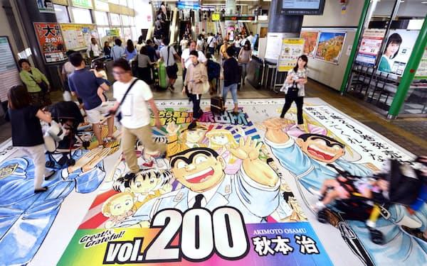 (写真はJR亀有駅の改札前に登場した単行本の広告)