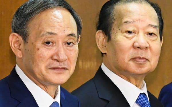 自民党臨時総務会で拳を合わせる二階幹事長(右)と菅新総裁