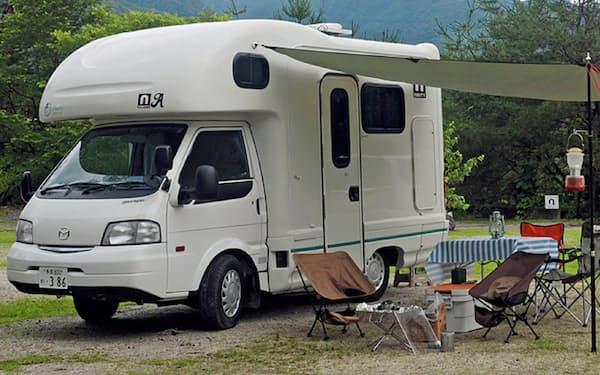 車体横にタープ生地を吸盤で貼り付けて屋根を作り、テーブルやイスを設置してくつろいだ