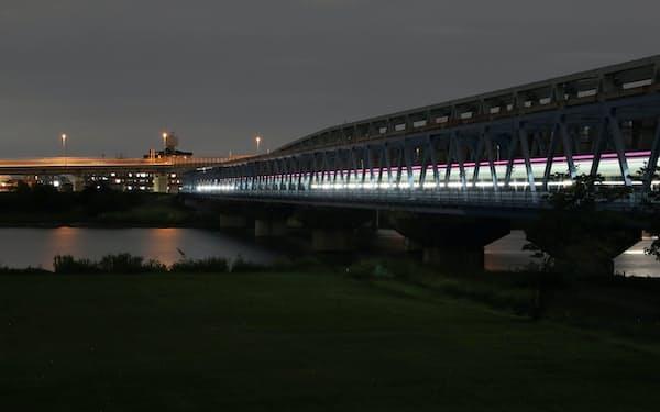 荒川にかかる鉄橋。通過する列車の明かりが高欄を照らす=山口朋秀撮影