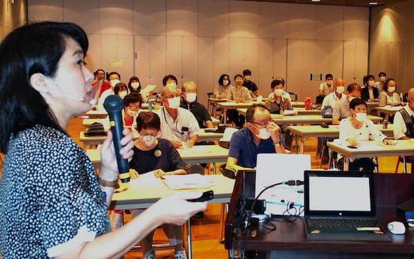 集まったシニアを前に福祉系職場の説明をする二瓶さん(9月、千葉県柏市内)