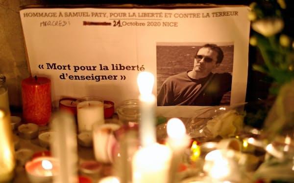 殺害された教師の追悼式がフランス各地で開かれている(21日、南仏ニース)=ロイター